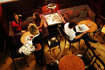 The picture shows a viennese coffeehouse seen from above. A waitress is carrying a tablet of coffee and water to a table where two women, seated in a velvet sofa, are talking. A man seated at the marble table next to them is reading a newspaper.