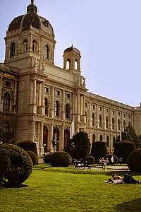 The picture shows people relaxing on the lawn in fron of the main entrance of the neo-baroque Museum of Art History